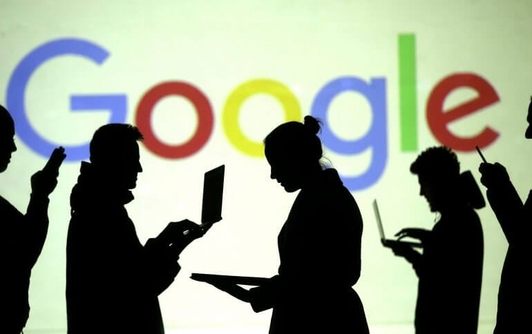 FILE PHOTO: Silhouettes of laptop and mobile device users in front of the Google logo in this picture illustration